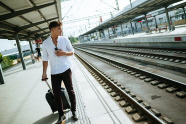 Young man with suitcase waiting at station platform - KIJF000561