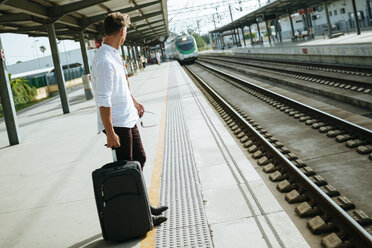 Young man with suitcase waiting at station platform - KIJF000564