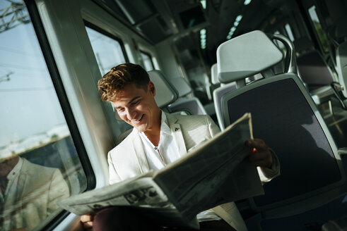 Young man reading a newspaper on a train - KIJF000567