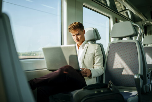 Young man using a laptop on a train - KIJF000570