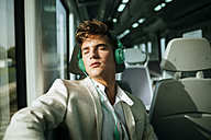 Young man with headphones sleeping on a train - KIJF000573