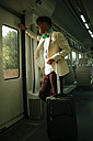 Young man looking out the door on a train - KIJF000576