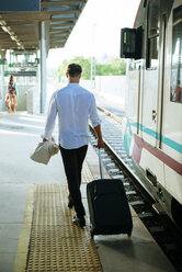 Young man leaving the train at a station - KIJF000579