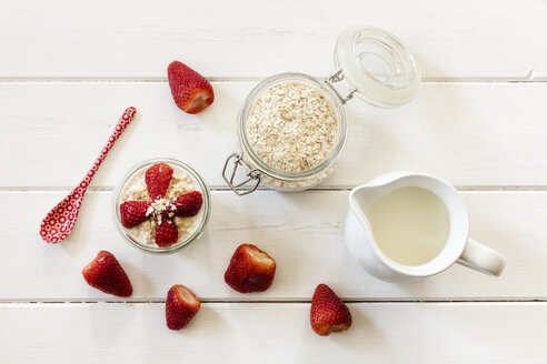 Glass of overnight oats with strawberries and milk jug on wood - EVGF003015