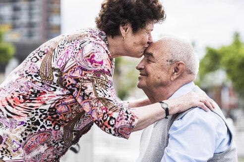 Senior woman kissing her husband - UUF008059