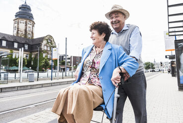 Germany, Mannheim, happy senior couple with wheeled walker waiting at station - UUF008080