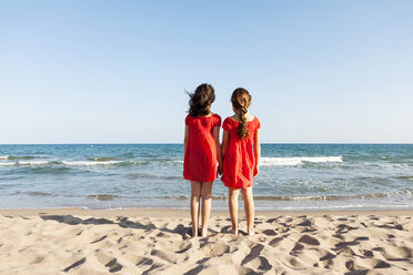 Back view of two little sisters standing at waterside on the beach looking to the sea - VABF000681