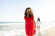 Happy little girl on the beach with her mother in the background - VABF000684