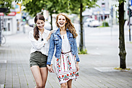 Two happy young women walking in the city - GDF001041