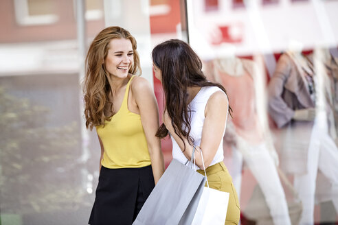 Two happy young women with shopping bags at shop window - GDF001044