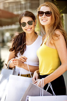 Two smiling young women holding shopping bags - GDF001047