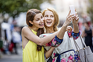 Two happy young women taking a selfie in the city - GDF001053