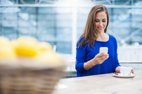 Smiling brunette woman with cup of coffee looking at cell phone - DIGF000590