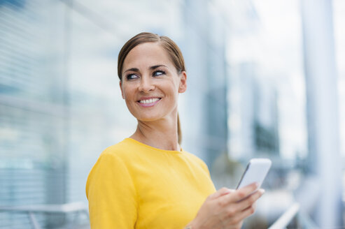 Smiling brunette woman holding cell phone - DIGF000602