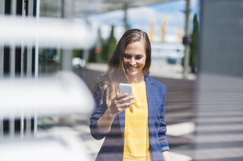 Smiling woman outdoors looking at cell phone - DIGF000617