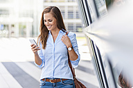 Smiling woman looking at cell phone outdoors - DIGF000623