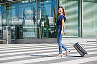 Smiling woman walking with luggage on zebra crossing - DIGF000629