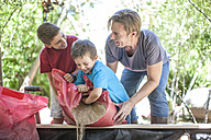 Father and sons filling sand into sandpit - ZEF009023