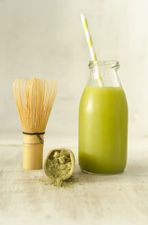 Glass bottle of Matcha smoothie, matcha powder and tea whisk - ODF001409
