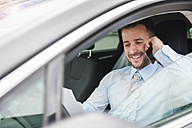 Smiling businessman with documents on cell phone in car - DIGF000646