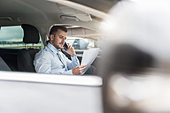 Businessman with documents on cell phone in car - DIGF000649