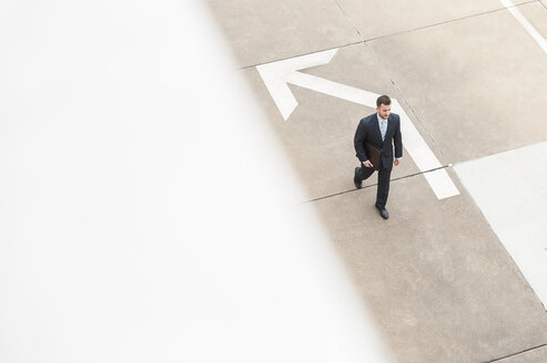 Businessman walking on paving with large arrow - DIGF000661