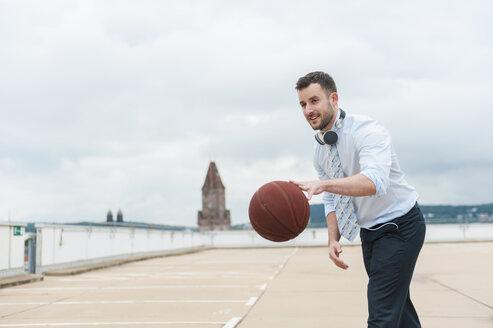 Businessman playing basketball outdoors - DIGF000673