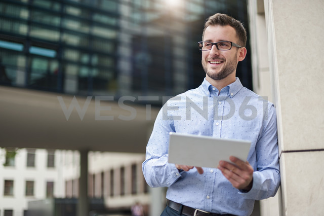 Smiling young man with digital tablet outdoors - DIGF000685