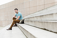 Smiling young man outdoors sitting on stairs listening to music - DIGF000694