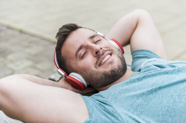 Relaxed young man lying on bench listening to music - DIGF000700