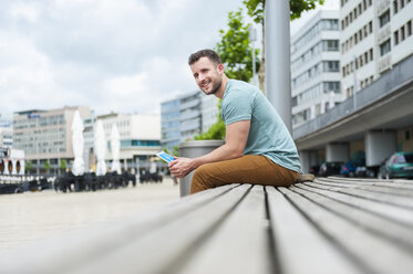 Smiling young man outdoors sitting on bench with digital tablet - DIGF000703