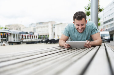 Smiling young man outdoors lying on bench using digital tablet - DIGF000706
