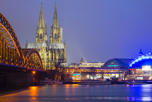 Germany, Cologne, view to lighted Cologne Cathedral with Hohenzollern Bridge in the foreground - WGF000889