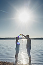 Couple standing at Lake Cospuden, forming heart with hands against the sun - MJF001975