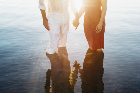 Couple holding hands, standing in water, against the sun - MJF001990
