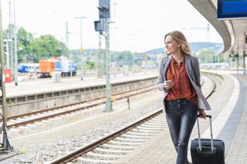 Young woman with smartphone and wheeled luggage walking at platform - DIGF000712