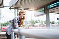 Smiling young woman at platform looking on cell phone - DIGF000715