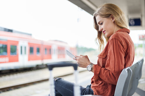 Young woman sitting on bench at platform using tablet - DIGF000718