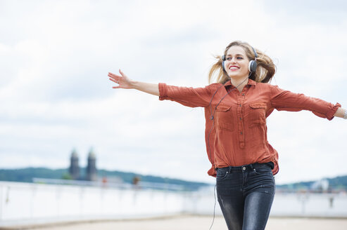 Happy woman with arms outstretched listening music with headphones - DIGF000727