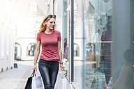 Young woman carrying shopping bags looking in shop window - DIGF000736