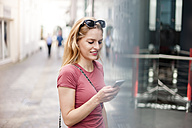 Young woman standing in front of shop window looking at her smartphone - DIGF000739