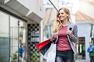 Smiling woman walking on the street carrying shopping bags - DIGF000742