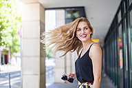 Portrait of smiling young woman tossing her hair - DIGF000745