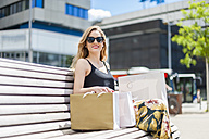 Portrait of smiling young woman sitting on a bench with shopping bags - DIGF000748