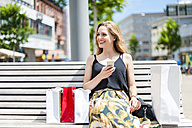 Portrait of smiling young woman sitting on a bench with shopping bags holding smartphone - DIGF000751