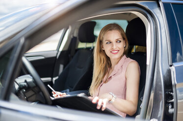 Portrait of smiling young businesswoman with cell phone and file sitting in her car - DIGF000754