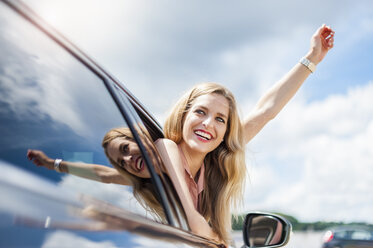 Portrait of smiling young woman leaning out of car window raising arm - DIGF000757