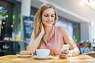 Portrait of smiling woman sitting in a sidewalk cafe looking at her smartphone - DIGF000760