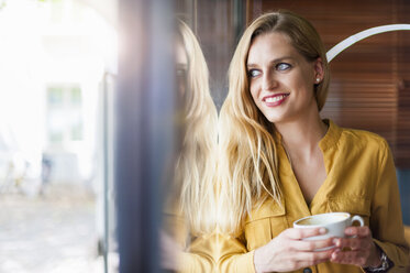 Portrait of smiling woman in a coffee shop looking through window - DIGF000766