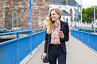 Smiling businesswoman walking on a bridge looking at her smartphone - DIGF000769